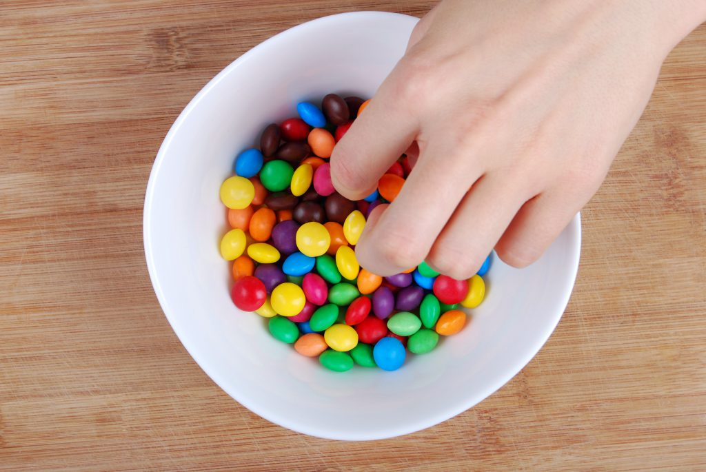 Hand in candy bowl