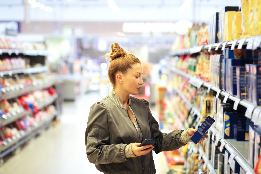 Woman looking at food package in supermarket