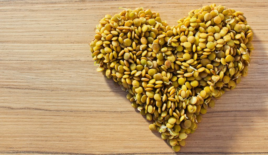Lentils forming a heart on wood background