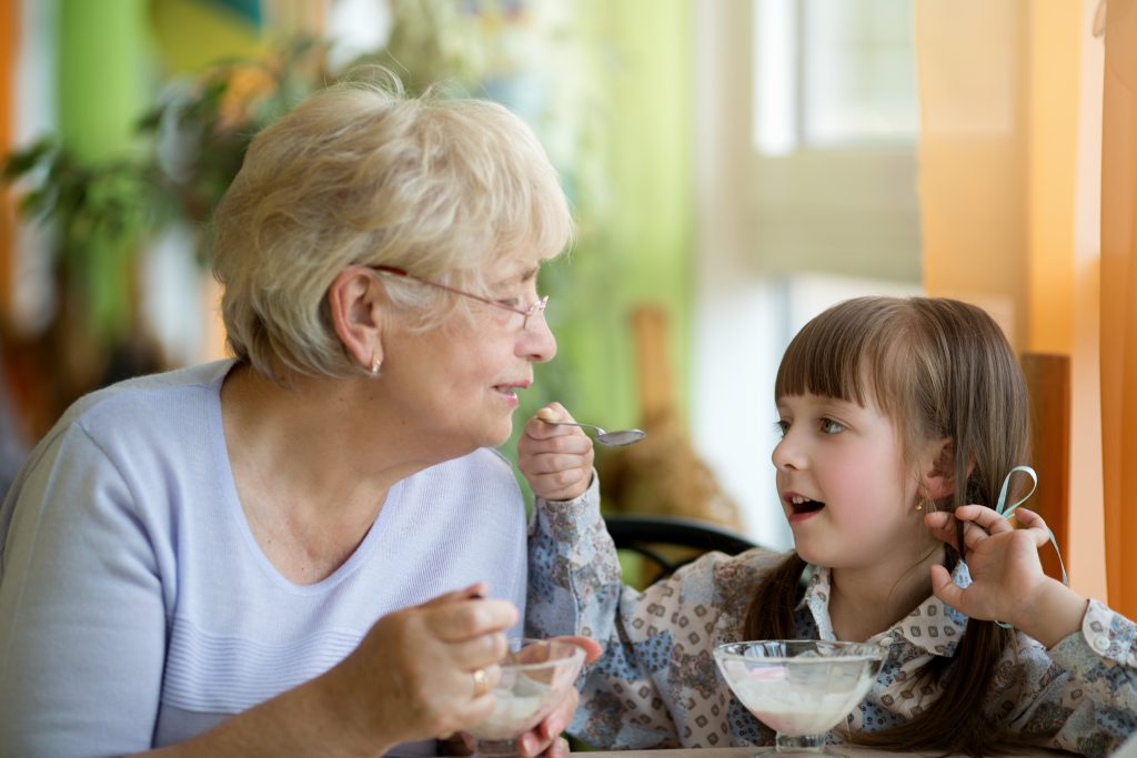 Grandchild sharing yogurt with grandmother