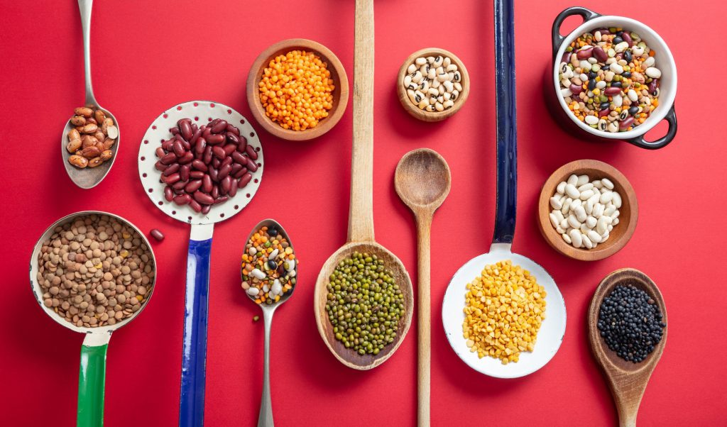Variety of legumes on red background