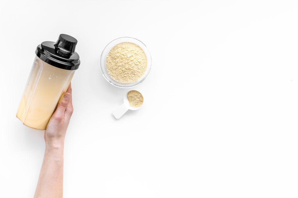 Hand holding supplement shaker near powder