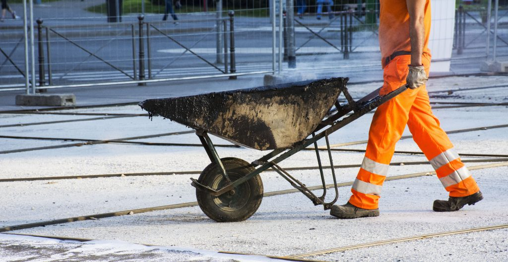 Man pushing wheelbarrow at construction site