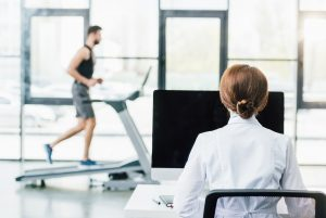 Researcher in front of computer measuring exercise performance of runner