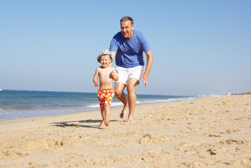 Man running with grandson on beach